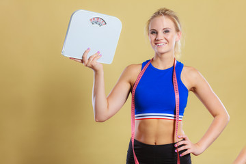 sporty happy woman with scale, weight loss