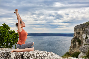 Young sportive woman training yoga asanas on rock above beautiful river.