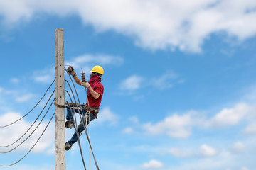 Electricians are climbing on electric poles to install power lines.