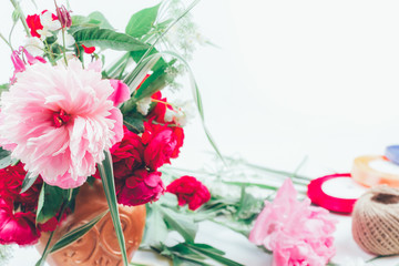 floral design. floral arrangement from  beautiful bouquet of pink flowers peons, cornflowers and red roses on white background with space for text