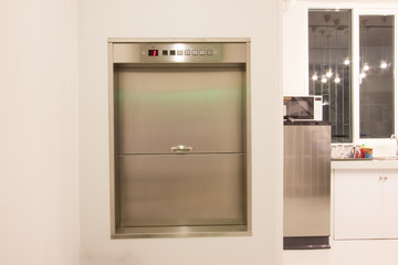Dumbwaiter lift elevator in a kitchen of rich house used for carrying food or goods