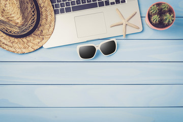 Laptop, sunglasses and straw hat on blue wooden table