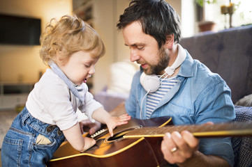 Father and son at home playing guitar together.