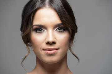 Close up horizontal portrait of young beautiful woman face smiling at camera with copyspace over gray studio background.