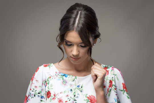 Young elegant woman with bun hairstyle touching hair lock looking down over gray studio background with vignette.