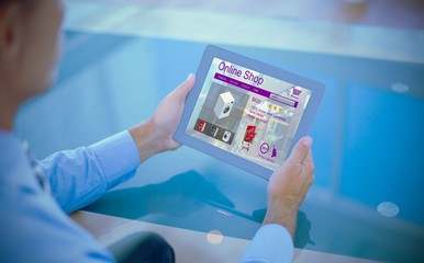 Composite image of businessman using his tablet
