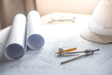 architectural drawing plan and blueprint rolls, project tool on work table, building construction industry concepts
