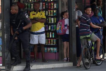 Residents react as a policeman takes up position during an operation against drug dealers in Cidade de Deus slum in Rio de Janeiro