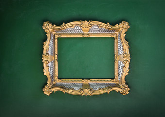 Old, victorian, gilded, decorative frame on a green wall, baroque, rococo, the Renaissance