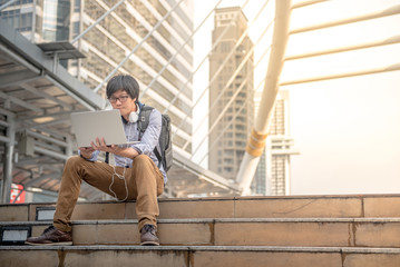 Young Asian business man dressed in casual style working with laptop computer in the city, digital nomad lifestyle and working outdoor concepts