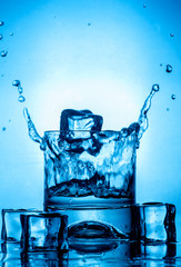 Ice splashing in a cool glass of water on blue background with ices front