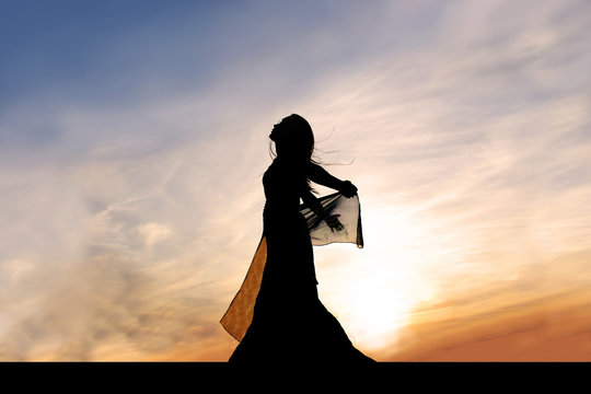 Silhouette of Beautiful Young Woman Outside at Sunset Praising God