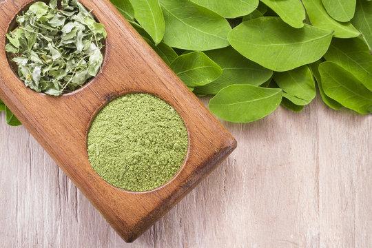 Leaves and moringa powder on wood (moringa oleifera)