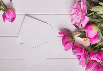 Beautiful pink peonies and paper envelope on white wooden table
