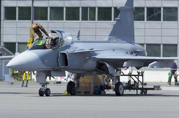 Pilot entering the cockpit of a modern jet fighter.