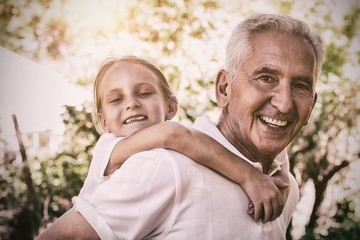 Portrait of smiling grandfather carrying granddaughter piggyback
