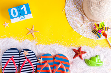 July 1st. Image of july 1 calendar with summer beach accessories and traveler outfit on background. Summer vacation concept
