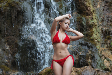 Girl in swimsuit at the waterfall