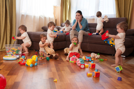 tired woman sitting on a sofa in the room. Child scattered toys. Mess in the house. a lot of children. the little girl plays in the room.