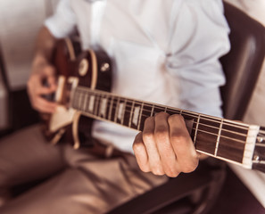 Handsome businessman playing guitar