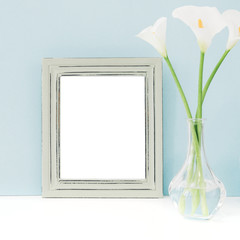 Empty wooden frame and flowers in vase on table on blue background. mock up