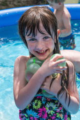 smiling young girl with water balloons in pool