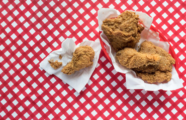 Fried chicken on plate with fork on red checkerboard tablecloth