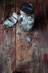 Money jar with dollars and change on old wooden table