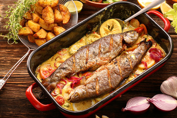 Baked fish with lemon sauce and vegetables in a pan