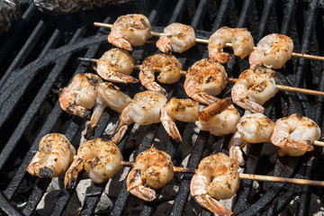 Shrimp kababs on round grill over hot coals