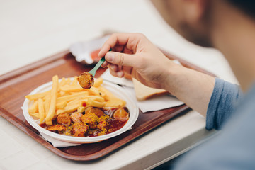 hands of a man eating a currywurst with a fries outdoor