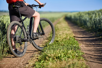 Close-up of cyclist man legs with mountain bike on the trail of field in the countryside.