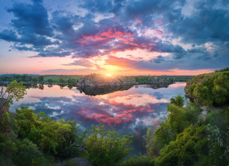 Wall Mural - Gorgeous scene with river, green trees, rocks and amazing blue sky with colorful clouds reflected in water at sunset. Fantastic summer landscape with lake, overcast sky and yellow sun in the evening