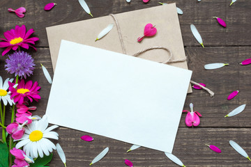 blank white greeting card and envelope with wildflowers bouquet and buds with petals around