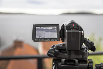 video camera shoots a landscape with a yacht