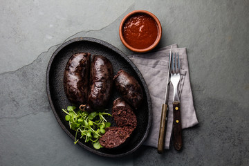 Bloody sausages, chilean prieta on cast iron plate with chili sauce. Slate background, top view