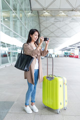 Woman taking photo with digital camera with luggage at airport