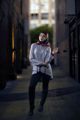 Woman wearing conservative Hijab fashion while walking in a modern urban city.  Depicts muslims who are proud to wear traditional clothing.