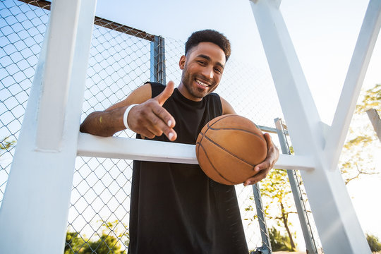 Handsome Strong man is holding ball on the basketball court.attractive,laugh,sport games,street ball,black,sport outfit,casual wear,black clothes
