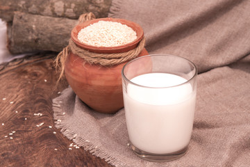 Sesame milk in glass and sesame seed in clay pot on a wooden table.
