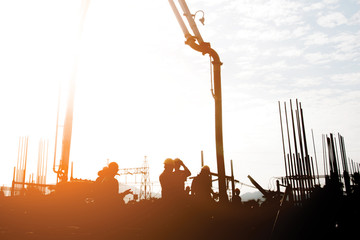 Silhouette construction industry team safely to work load concrete building according to set goal over blurred background sunset pastel for industry background.