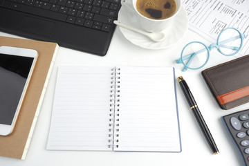 The blank page notebook on white desktop with pen, coffee, laptop, book, calculator, glasses and mobile phone