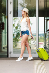 Attractive woman tourist with suitcase walking from flight