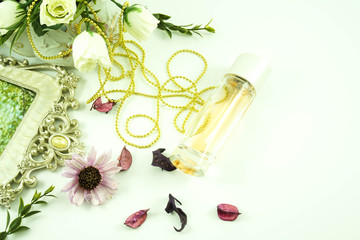 Perfume bottles with white rose flowers on light background. fragrance cosmetics, fragrance collection. Free space for text. Gold concept