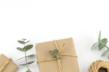 Brown gift boxes and ropes decorated with baby eucalyptus leaves with copy space on white background