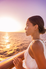Wall Mural - Cruise luxury travel woman europe destination vacation holiday. Girl enjoying sunset view in elegant white evening dress from balcony suite deck. Asian beauty relaxing.