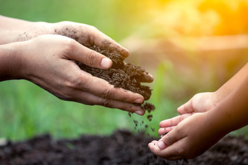 Mother's hand giving soil to a child for planting together in vintage color tone