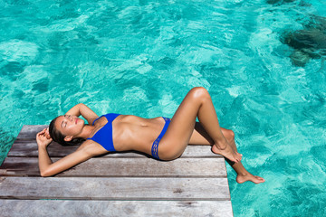 Wall Mural - Luxury travel woman tanning on overwater resort deck over turquoise ocean water in Tahiti, French Polynesia island. Vacation destination.