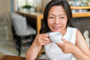 Mature Asian woman drinking english breakfast tea relaxing at cafe. Chinese middle-aged lady enjoying city lifestyle, stylish living.