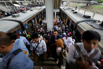 Commuters walk during the morning rush after arriving at Tanah Abang train station in Jakarta